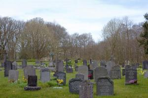 Small country graveyard with multiple gravestoness in a grassy enclosure